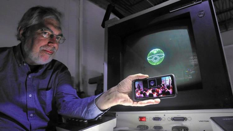 "UIC graduate and Aura Technologies President Steve Heminover holds a phone with a scene from the original ""Star Wars"" beside an image of the Death Star on the computer that was used to create digital effects for a small part of the 1977 film."